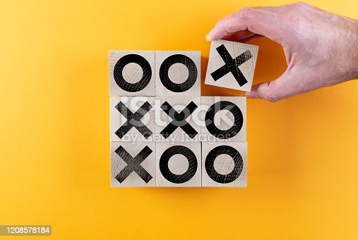 top view of tic-tac-toe game on wooden toy blocks against orange background, winning and scoring concept