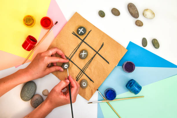 top view of tic tac toe game with stones marked with naughts and crosses. Children's art project, a craft for children. DIY concept. Step by step. Step 6 stock photo