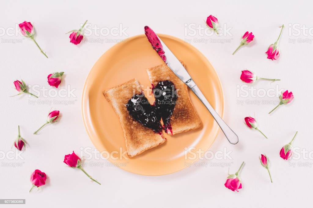 top view of toast with jam and knife on yellow plate isolated on white, valentines day concept - Royalty-free Baking Stock Photo