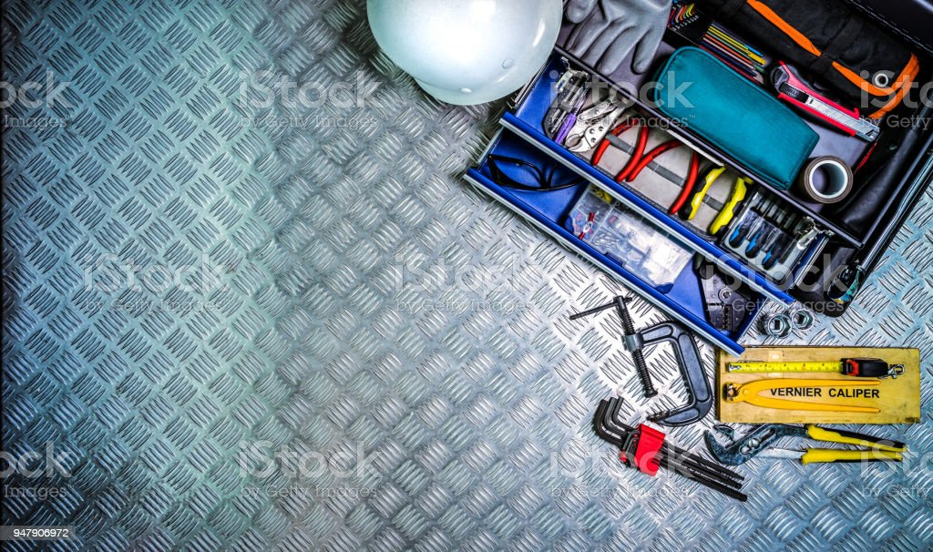 Top view of tools box and helmet on checkered plate background in workshop. Service tools set. Home building and electrical tools. Plumber hand tools. Technician equipment for repair work. stock photo