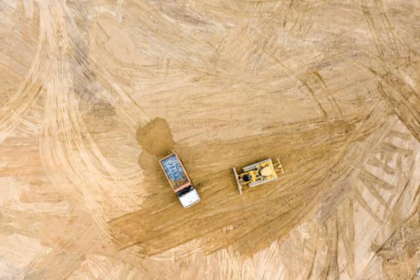 ansicht des gleisbulldozer-nivellierungsbodens vor dem straßenbau - aerial overview soil stock-fotos und bilder