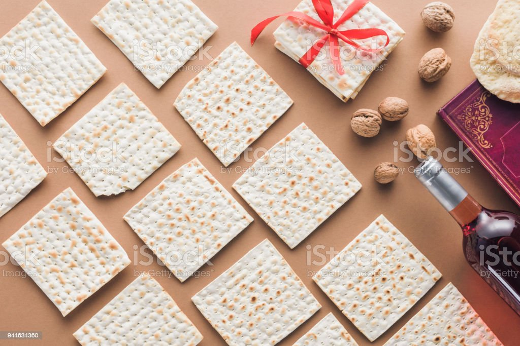 top view of traditional book with text in hebrew and collection of matza on brown table stock photo
