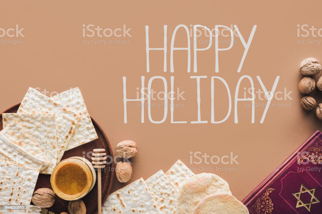top view of traditional book with text in hebrew and happy holiday greeting stock photo