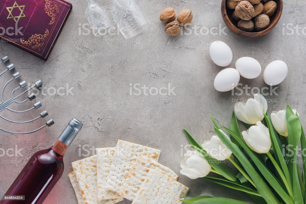 top view of traditional book with text in hebrew and matza on concrete table stock photo