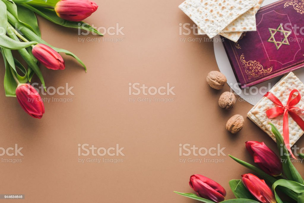 top view of traditional book with text in hebrew, bouquets of red tulips and matza on table stock photo