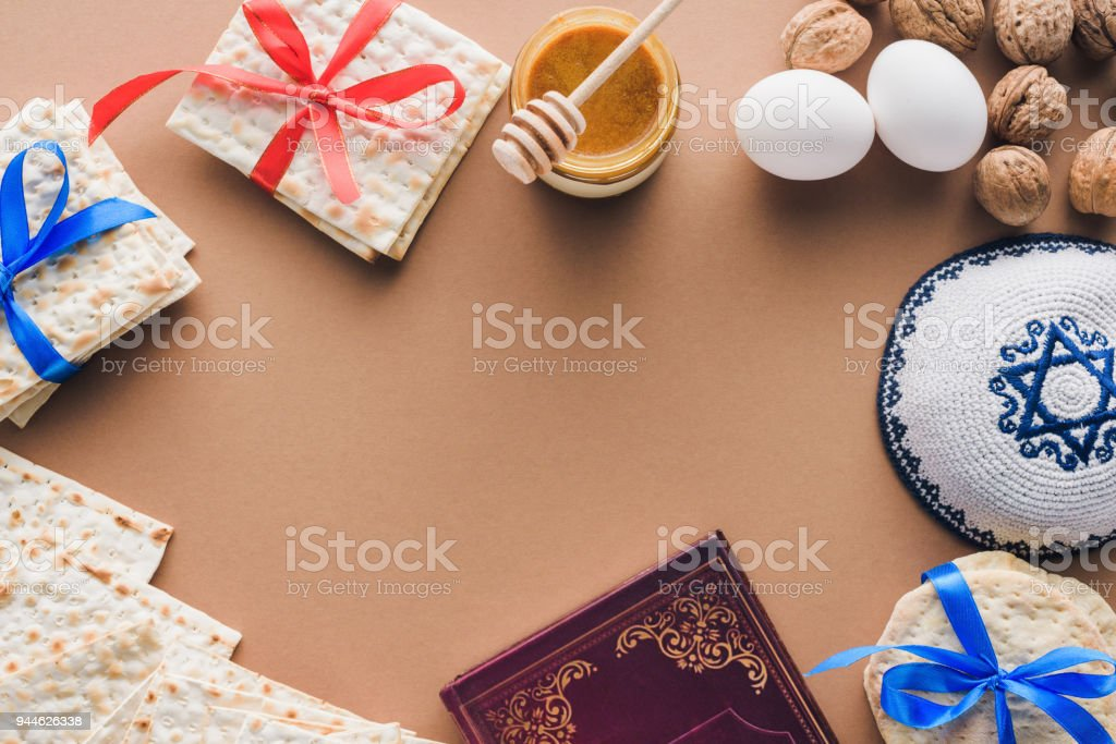 top view of traditional book with text in hebrew, kippah and matza on brown table stock photo