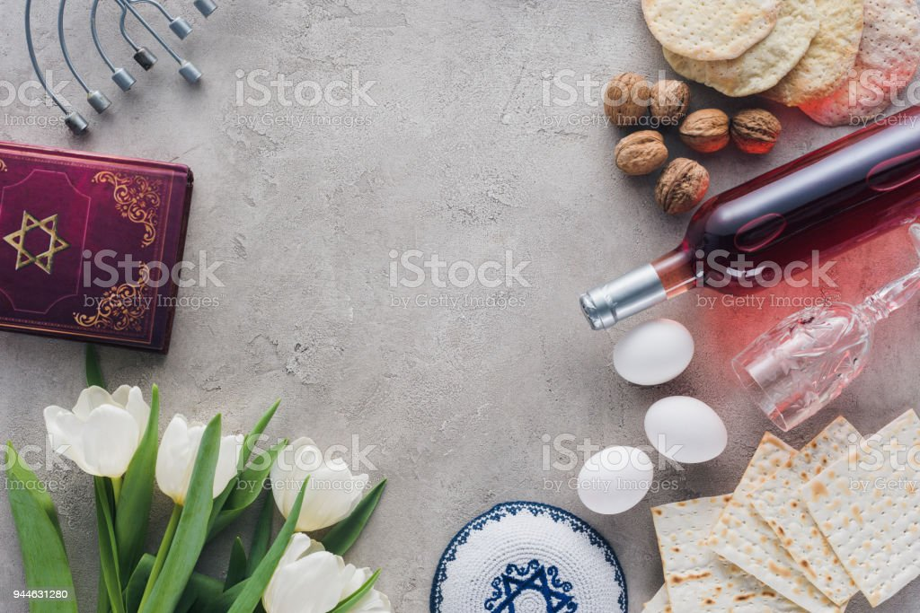 top view of traditional book with text in hebrew, kippah and menorah on concrete table stock photo