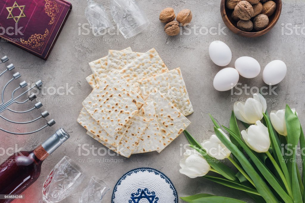 top view of traditional book with text in hebrew, matza and menorah on concrete table stock photo