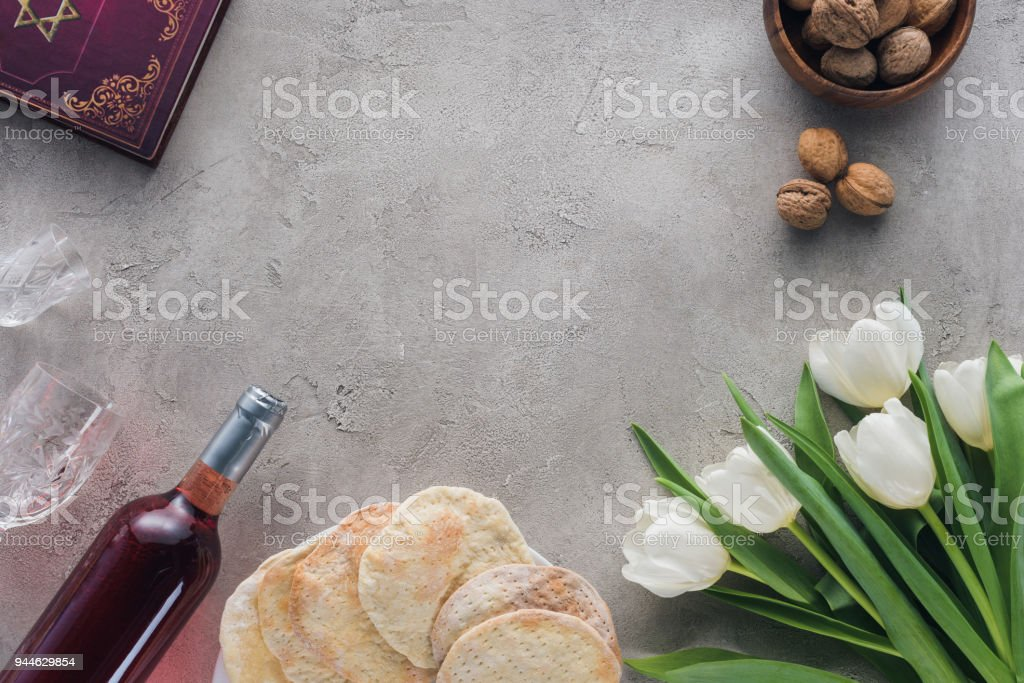 top view of traditional book with text in hebrew, matza and wine on concrete table stock photo