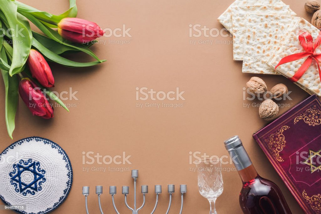 top view of traditional book with text in hebrew, menorah and kippah on brown surface stock photo