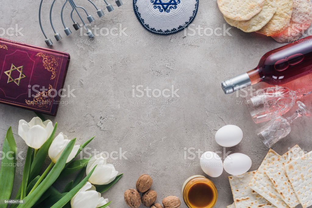 top view of traditional book with text in hebrew, menorah and kippah on concrete table stock photo
