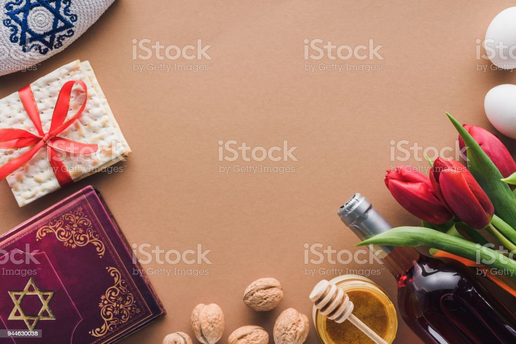 top view of traditional book with text in hebrew, wine and matza on brown table stock photo