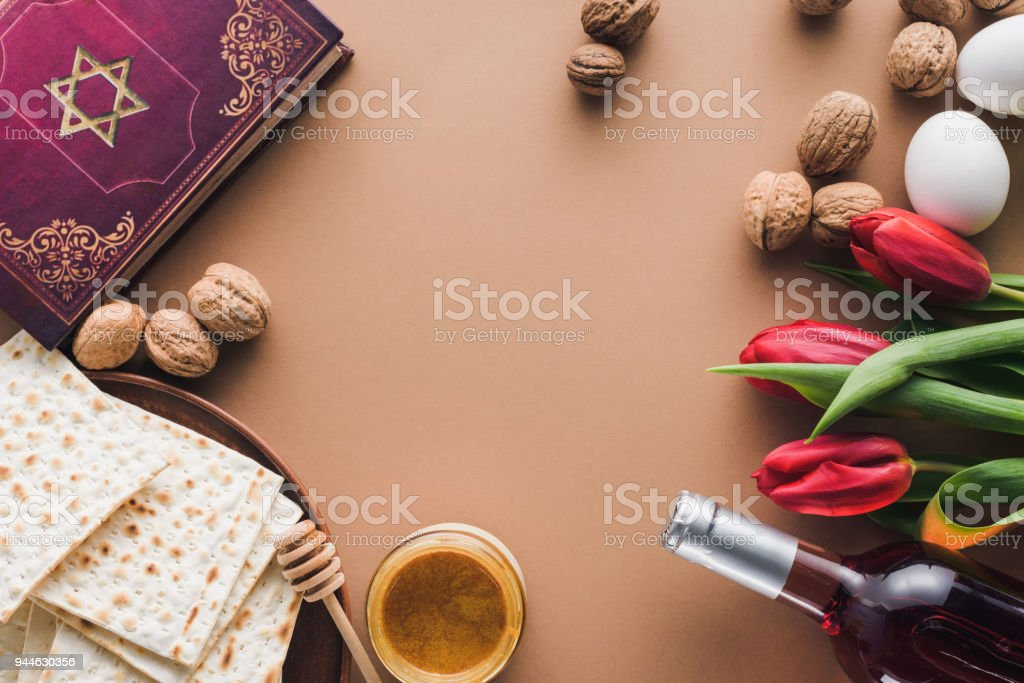 top view of traditional book with text in hebrew, wine and matza on tabletop stock photo