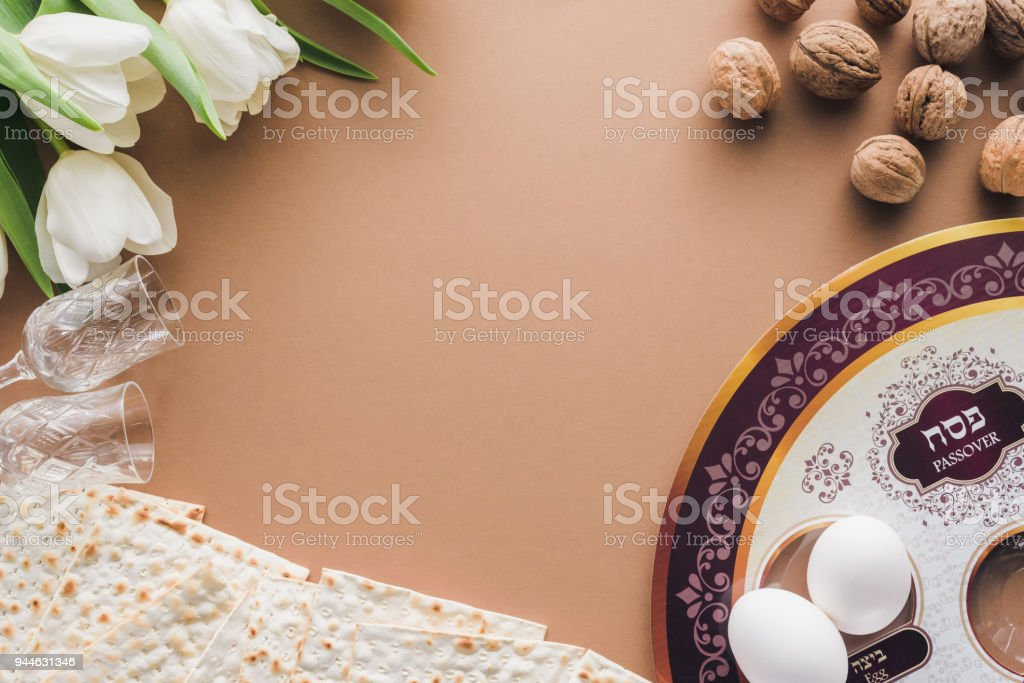top view of traditional jewish plate and matza on beige table, Passover Haggadah concept stock photo
