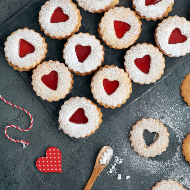 Top view of traditional Linzer cookies with red jam heart on dark textured background stock photo