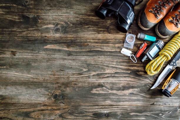 Vue de dessus de l'équipement de voyage et des accessoires pour le voyage de randonnée de montagne sur le plancher en bois faisant un cadre avec l'espace de copie - Photo