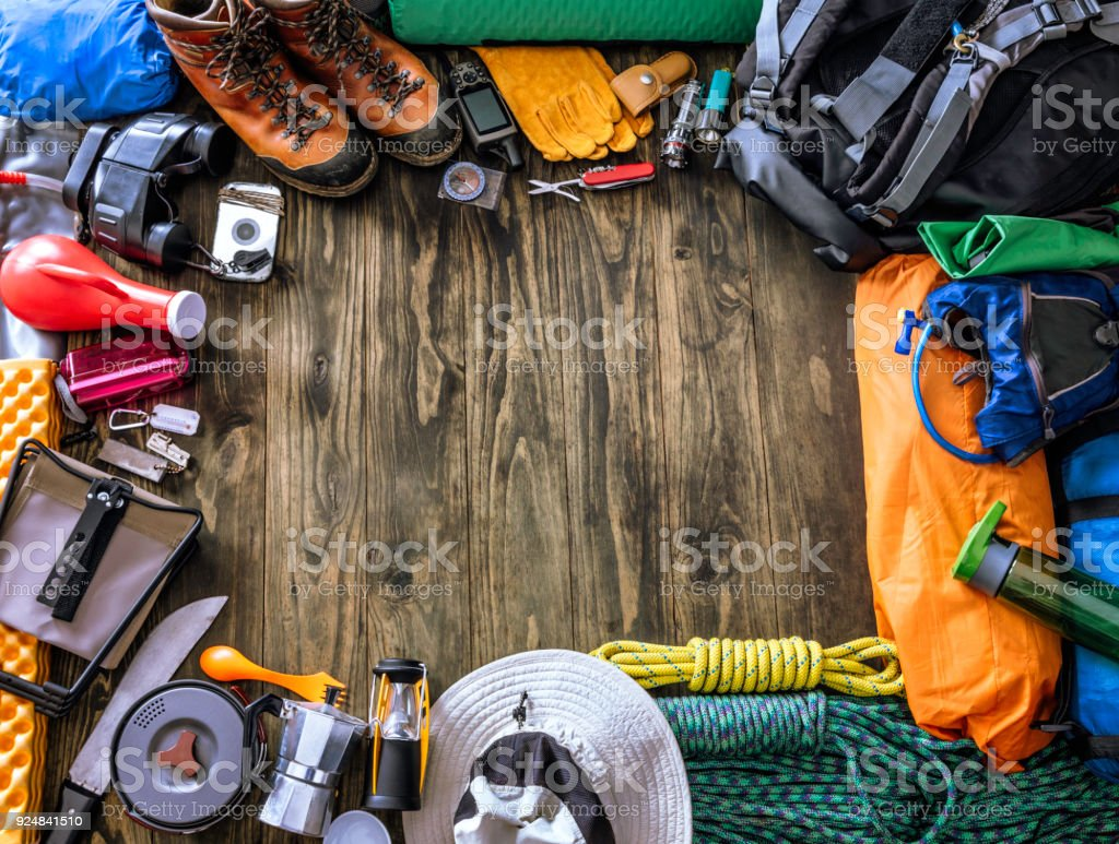 Top view of travel equipment and accessories for mountain hiking trip on wood floor. Frame set with copy space. stock photo