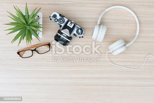 Top view of travel stuff. Camera, headphones and glasses on wood table with copy space