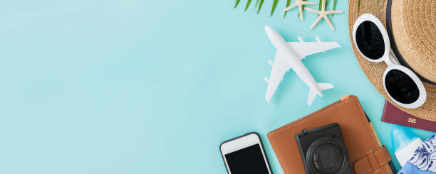 top view of traveler accessories, tropical palm leaf and airplane on blue background with empty space for text. travel summer holiday vacation banner concept. - phone, travelling, copy space imagens e fotografias de stock