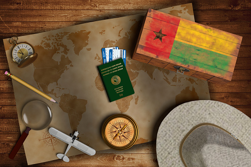istock Top view of traveling gadgets, vintage map, magnify glass, hat and airplane model on the wood table background. On center, official passport of Guinee Bissau and your flag. 1203627589