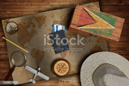 istock Top view of traveling gadgets, vintage map, magnify glass, hat and airplane model on the wood table background. On center, official passport of Guyana and your flag. 1203627620