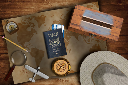 istock Top view of traveling gadgets, vintage map, magnify glass, hat and airplane model on the wood table background. On center, official passport of Botswana and your flag. 1218276342