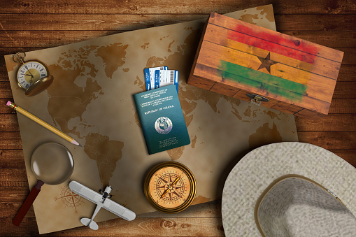 istock Top view of traveling gadgets, vintage map, magnify glass, hat and airplane model on the wood table background. On center, official passport of Ghana and your flag. 1218276386