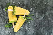 Top view of tree summer fruit popsicles with mango, kiwi and chia seeds over textured grey background. The concept of organic and healthy food.
