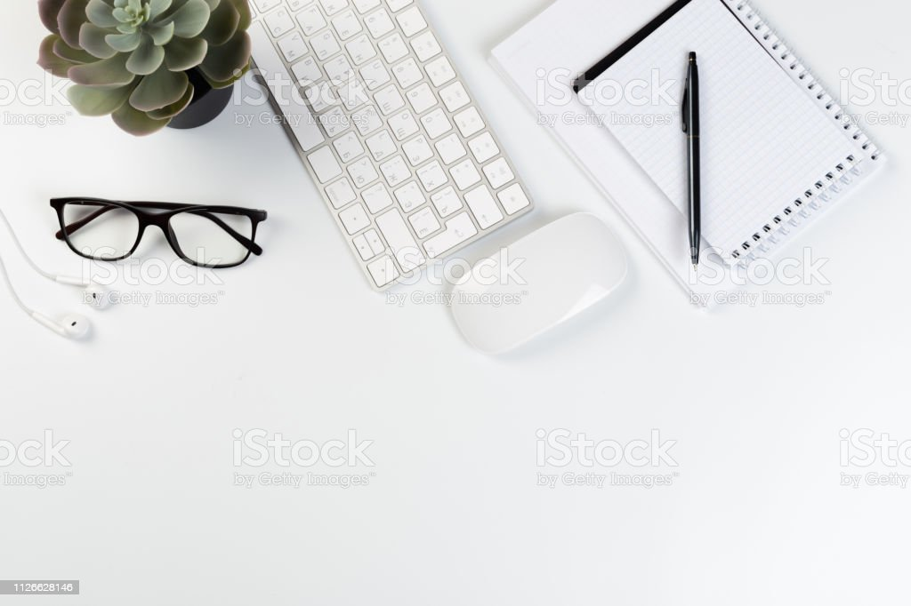 Top View of trendy White Office Desk with keyboard, white earphones...