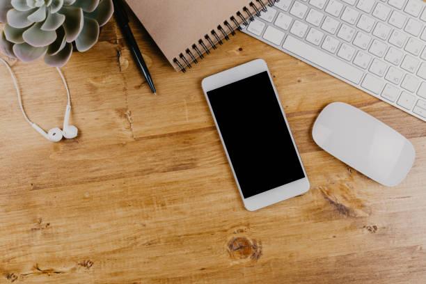 ovanifrån av trendiga trä office skrivbord med tangentbordet, vita hörlurar och kontorsmaterial - skrivbord bildbanksfoton och bilder