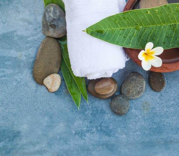 draufsicht der tropische weiße blume mit steinen für massage-behandlung auf blauem marmor hintergrund. - steingut geschirr stock-fotos und bilder