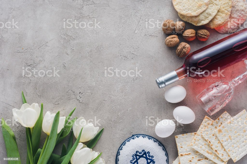 top view of tulips, kippah and matza on concrete table, jewish Passover holiday concept stock photo