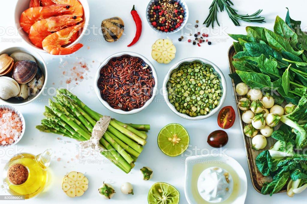 Draufsicht von Thunfisch und Lachs-Sashimi, gekochte Garnelen, Klemmen, brauner Reis, Spargel, Spinat, Aubergine, weiß, Salz und Pfeffer. – Foto