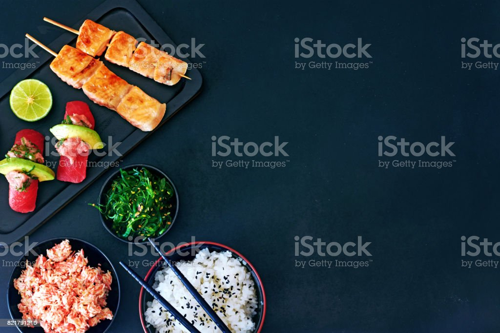Top view of tuna sushi, grilled salmon on skewers, bowl or rice, crab meat and wakame salad over dark board with a copy space. stock photo