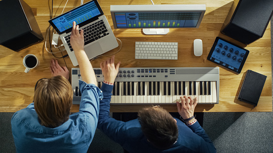 Top View of Two Audio Engineers Working in Their Sunny Studio. They Play on a Musical Keyboard and Experiment with Sound.