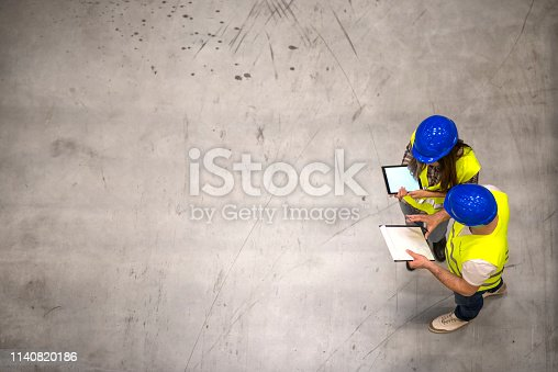 521012560istockphoto Top view of two construction workers wearing hardhats and reflective jackets holding tablet and checklist on gray concrete background. Group of engineers sharing ideas about the project. 1140820186
