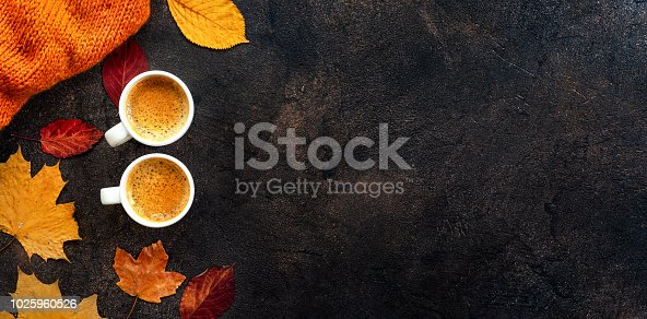 Top view of two cups of coffee around yellow leaves on dark background. Copy space