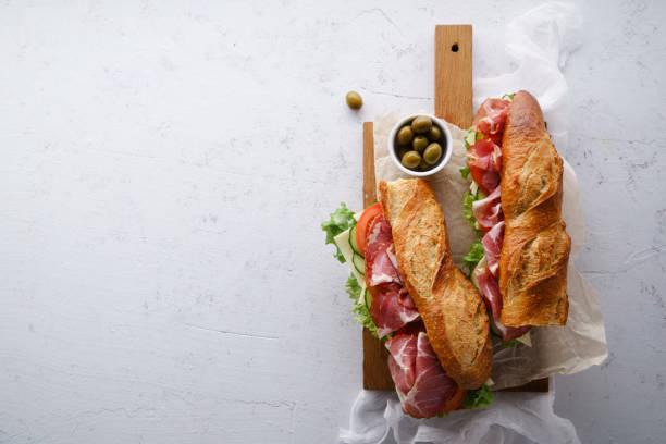 vista superior de dos fresco baguette sándwiches bahn-mi estilo. jamón, rodajas de queso, tomates y lechugas frescas en tabla de cortar madera oscuro sobre fondo concreto. - tienda delicatessen fotografías e imágenes de stock
