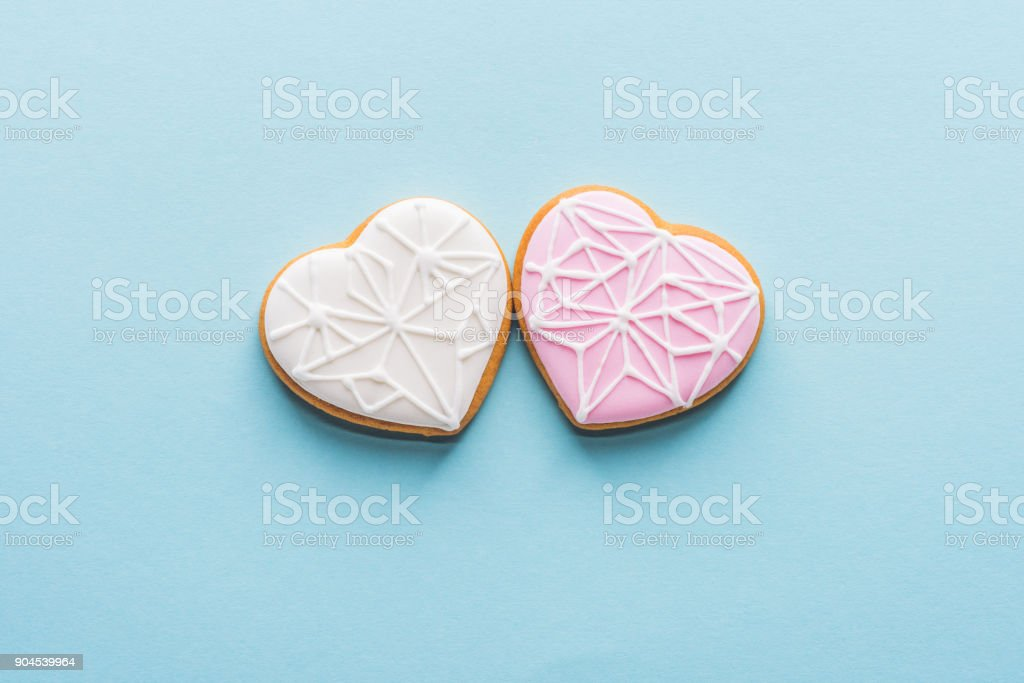 top view of two glazed heart shaped cookies isolated on blue, st valentines day holiday concept stock photo