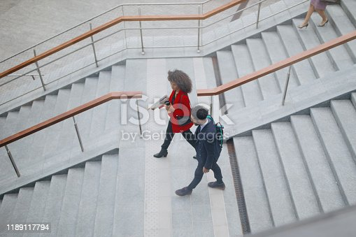 Top view of two people going down the stairs