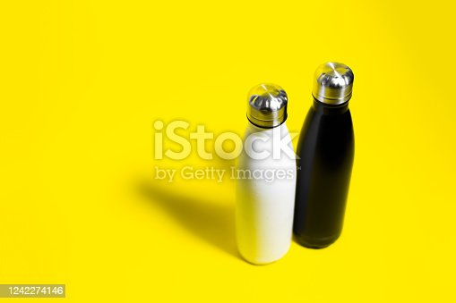 1129148925 istock photo Top view of two reusable eco, steel stainless, thermo water bottle, white and black color, isolated on yellow background. 1242274146