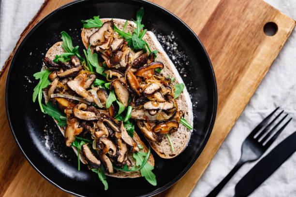 Top view of two vegan sandwiches with fresh arugula, fried shiitake mushroom and shallot onion. stock photo