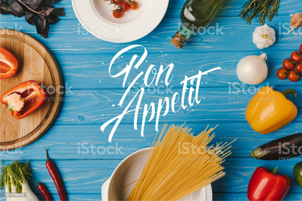 top view of uncooked pasta and vegetables on blue table, bon appetit lettering stock photo