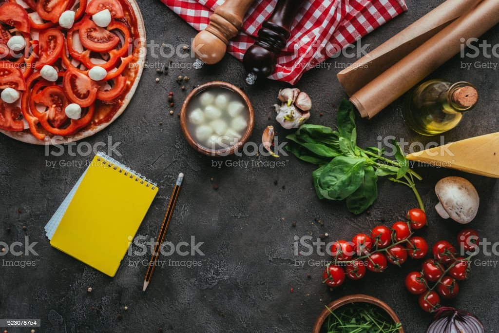 Top view of uncooked pizza with notebook for recipe on concrete top view of uncooked pizza with notebook for recipe on concrete table royalty free stock forumfinder Image collections