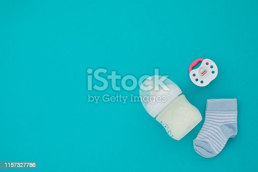 Set for a newborn nipple bottle and socks blue background top view