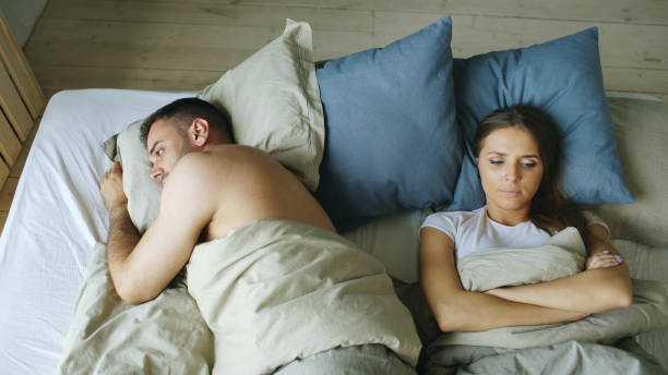 Top view of upset lying sleepless couple in bed offended because of quarrel Top view of upset lying sleepless couple in bed offended because of quarrel at home erectile dysfunction stock pictures, royalty-free photos & images