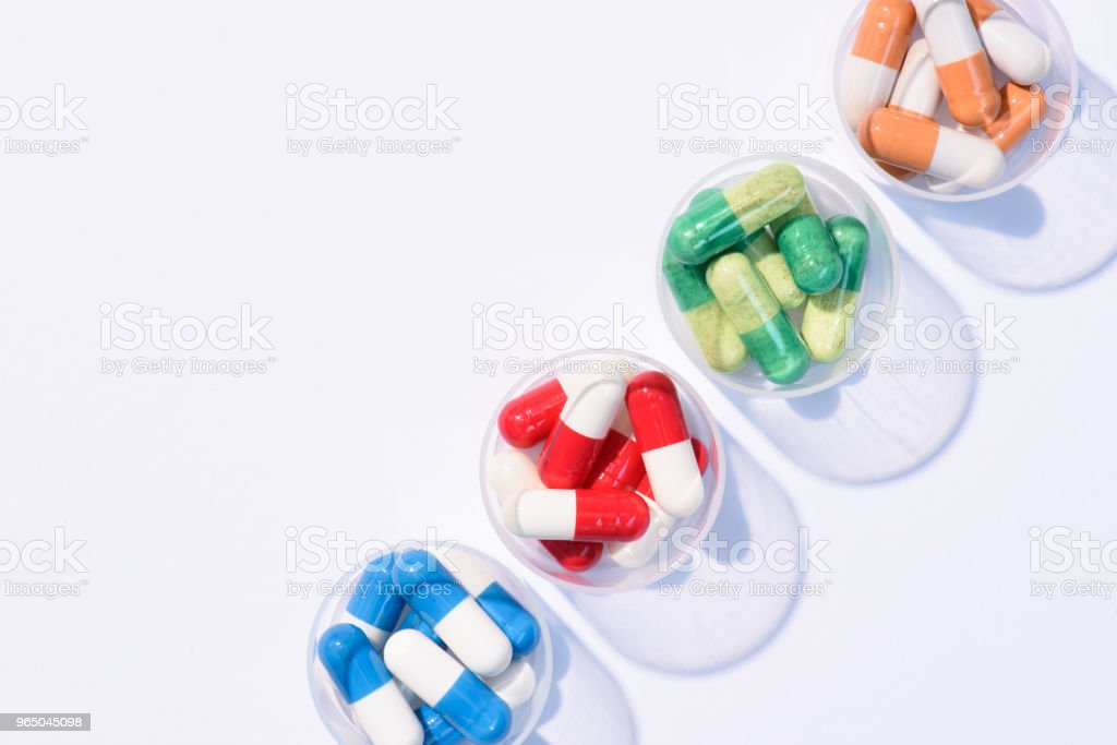 top view of various colorful pills in plastic bowls in row on white royalty-free stock photo