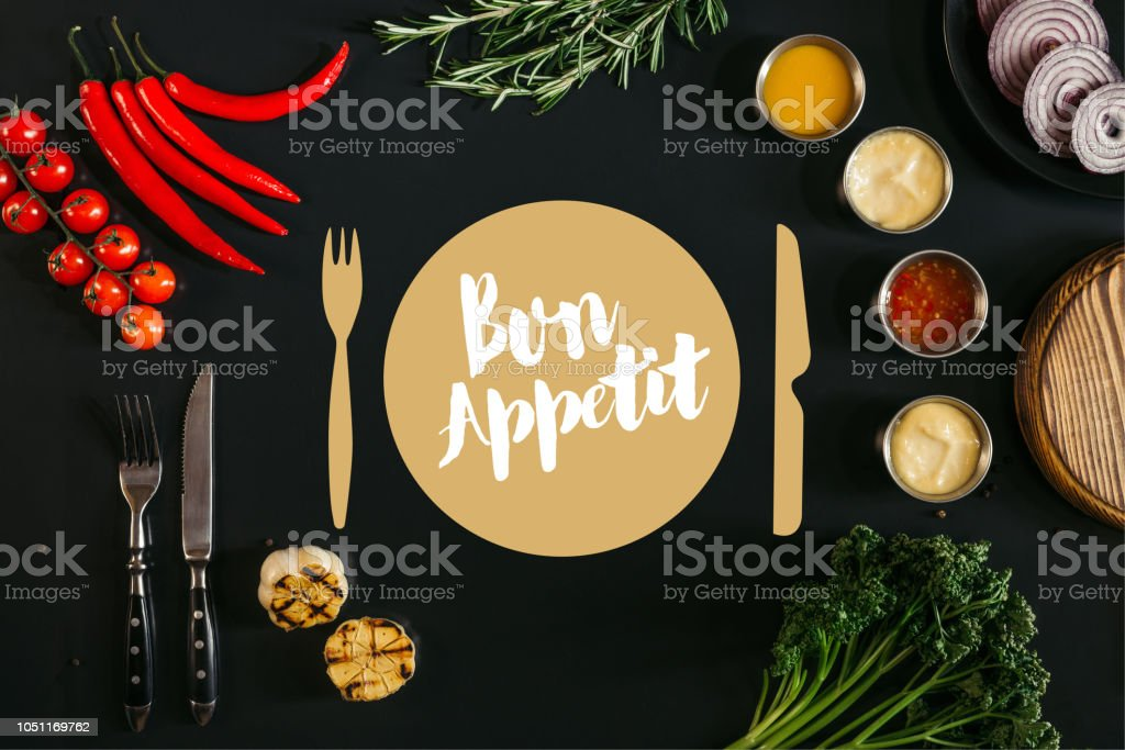 top view of various sauces, grilled garlic, fork with knife and fresh vegetables with herbs on black background with 'bon appetit' lettering stock photo