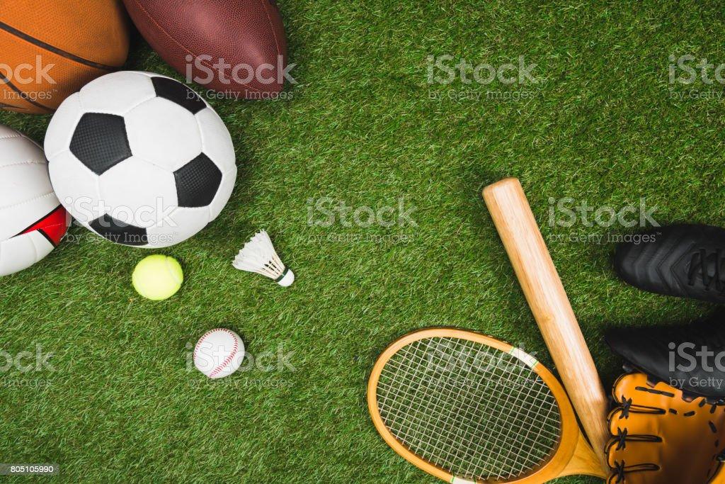 top view of various sport balls, baseball bat and glove, badminton racket on green lawn royalty-free stock photo