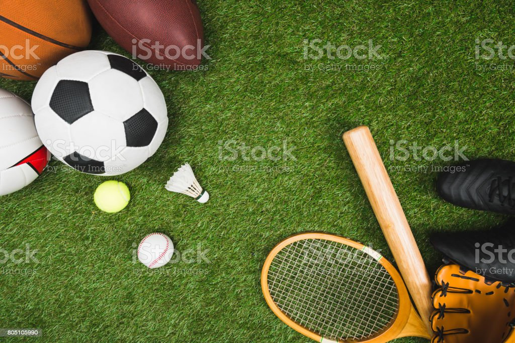 top view of various sport balls, baseball bat and glove, badminton racket on green lawn - foto stock